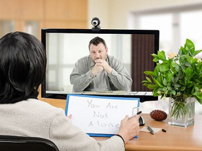 Middle aged man sitting in the monitor talks with psychotherapist via online video chat. He looking depressed. Black-haired psychiatrist holds written message for him - You are not alone. Horizontal shot indoors